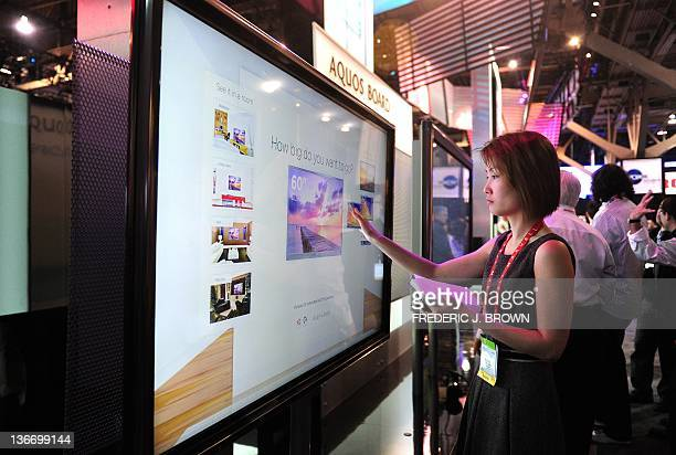 A woman touches the screen on Sharp's 80inch touch screen TV set Aquos Board an Interactive Display System on the opening day of the International...