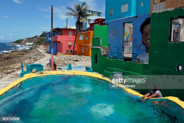 A woman touches the water of a makeshift pool in the neighbourhood of La Perla where the video 'Despacito' was recorded in San Juan on July 22 2017...