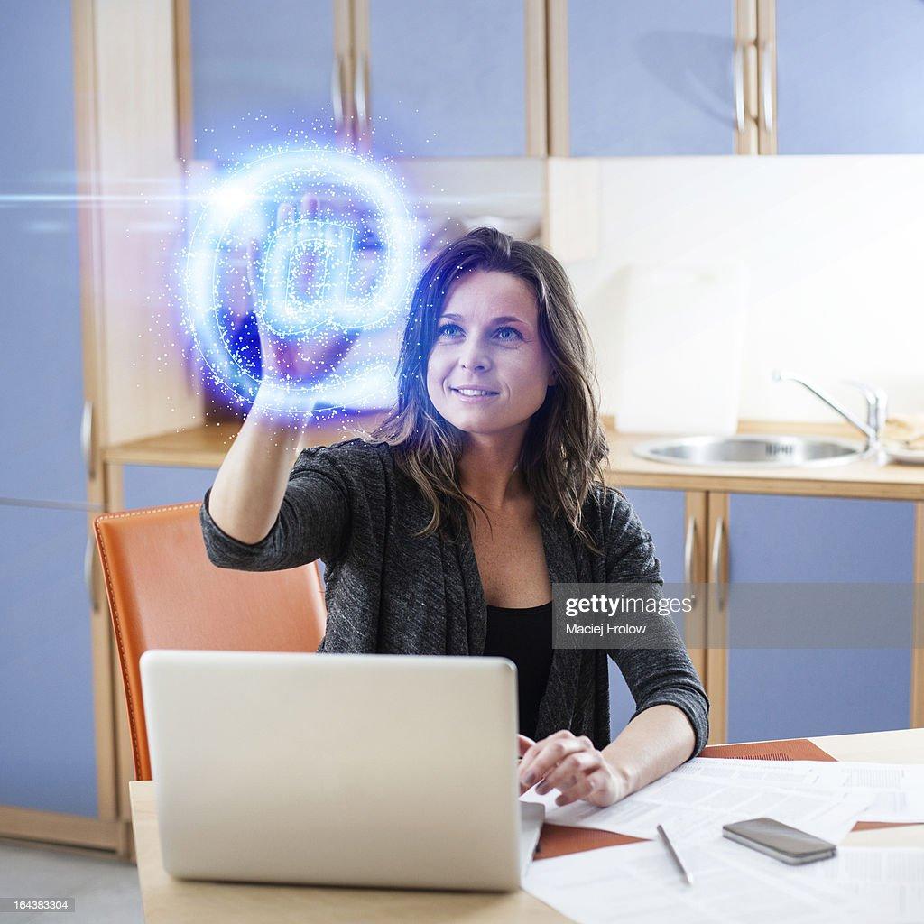 Woman touching a virtual @ symbol : Stock Photo