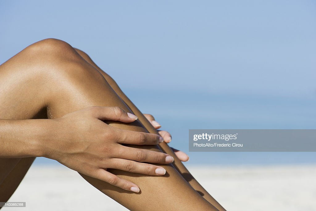 Woman touching bare legs at the beach, cropped : Stock Photo