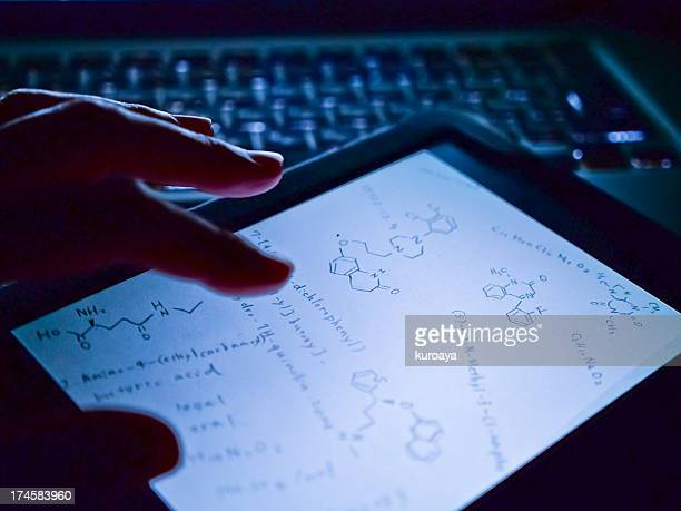 Woman touching chemical formula on digital tablet