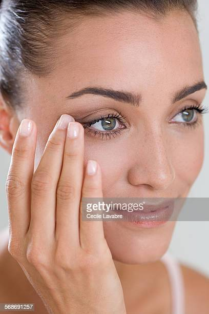 Woman touching eye wrinkles with finger