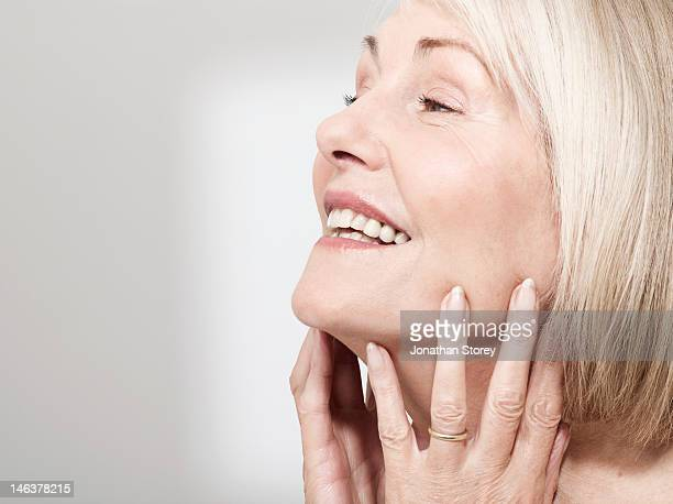 M woman touching face with both hands, chin upu
