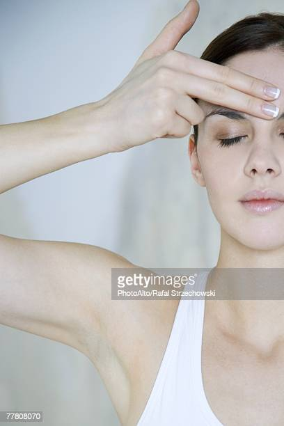 Woman touching forehead, eyes closed, cropped view