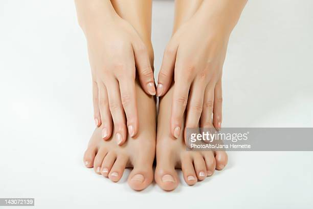 Woman touching her bare feet, cropped