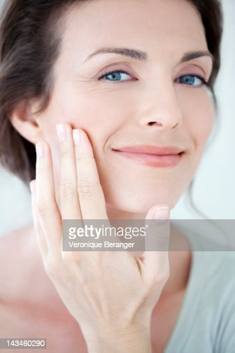 Woman touching her cheek : Stock Photo