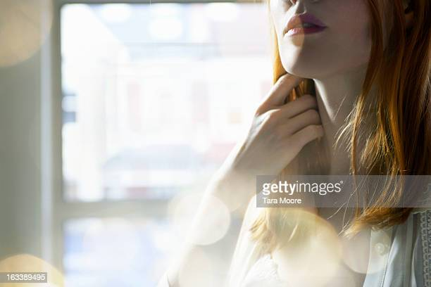 woman touching her hair with lens flare