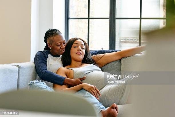 Woman touching her pregnant partner's stomach