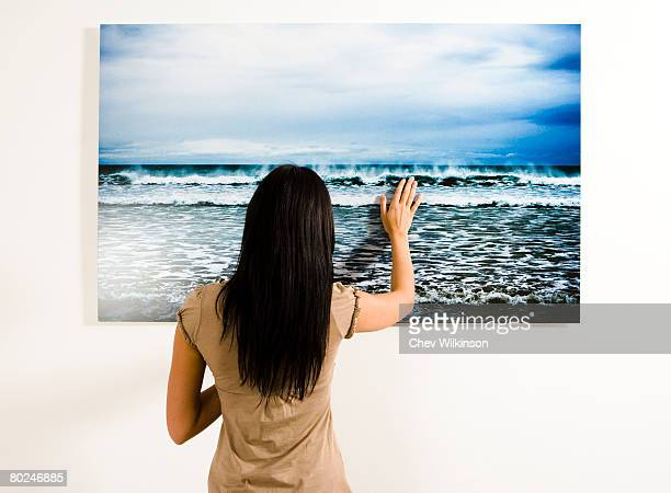 Woman touching photograph of the sea.