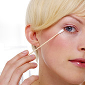Woman touching up eyeliner with cotton swab