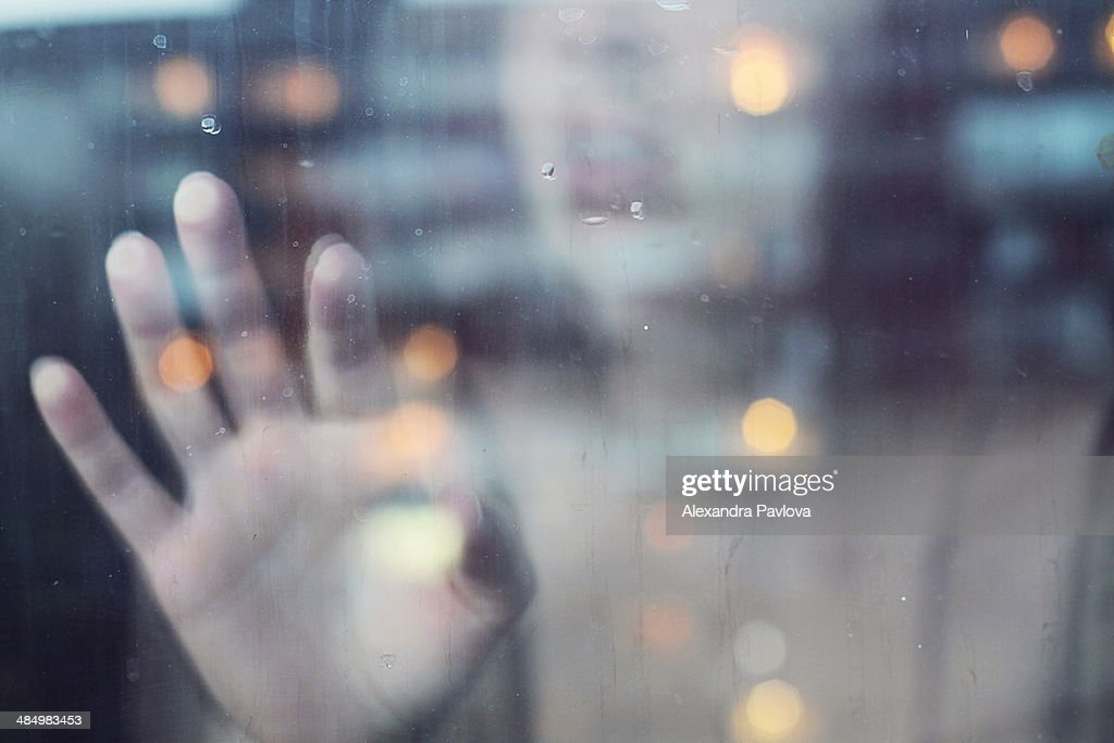Woman touching window from inside