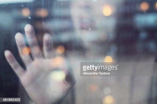 Woman touching window from inside