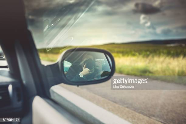 Woman tourist taking photo in car with camera driving on road trip travel