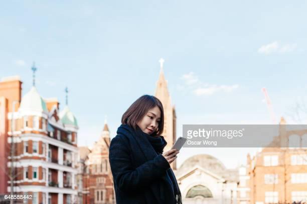 Woman tourist using phone against cityscape