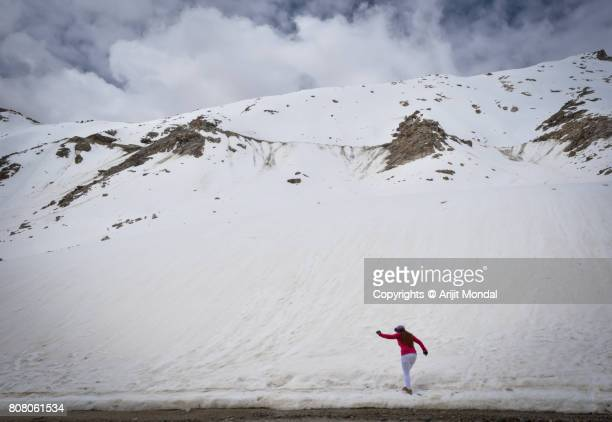 Woman Tracking Snow Mountain and Glacier at Khardungla Pass in summer, Leh Ladakh Region, Jammu Kashmir, India
