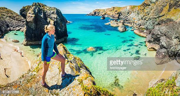 Woman trail runner overlooking idyllic ocean beach bay cliffs panorama
