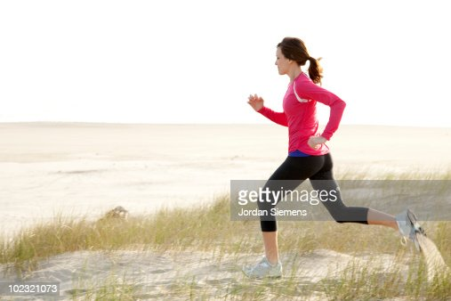 Woman trail running along the Oregon coast.  : Stock Photo