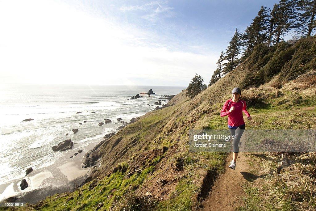Woman trail running along the Oregon coast.
