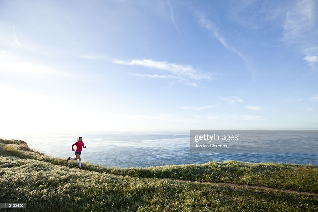 Woman trail running near the ocean. : Stock Photo