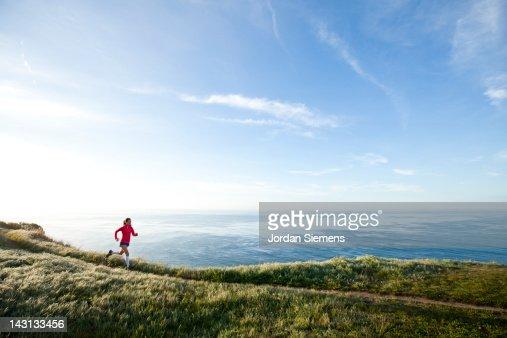 Woman trail running near the ocean.