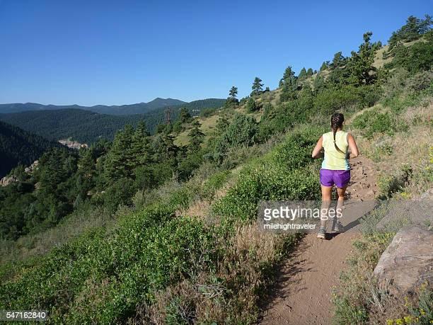 Woman trail runs Mount Falcon Morrison Colorado Rocky Mountains
