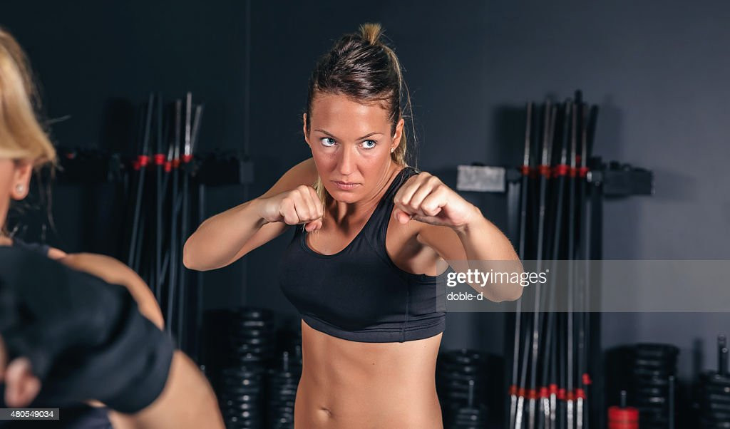 Woman training hard boxing in the gym : Stock Photo