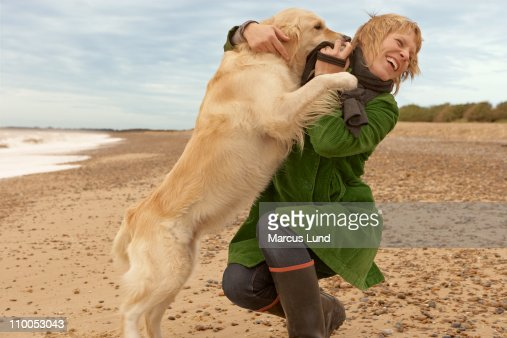 Woman training, playing with dog, beach : Stock Photo