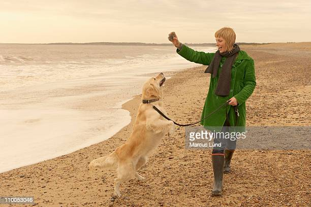 Woman training, playing with dog, beach