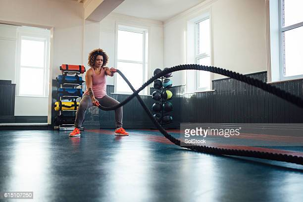 Woman Training with Battle Ropes in the Gym
