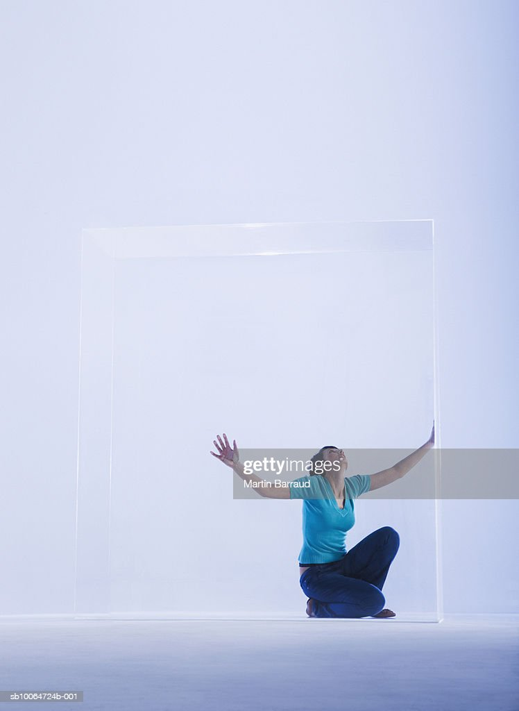 Woman trapped in glass cabinet, looking up