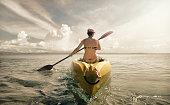 Woman in bikini exploring calm tropical beach by canoe.