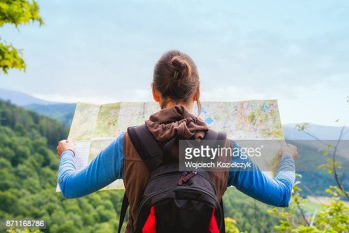 Woman traveler with backpack checks map to find directions in wilderness area, real explorer. Travel Concept : Stock Photo