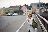 A woman traveler with backpack on a street in a European city