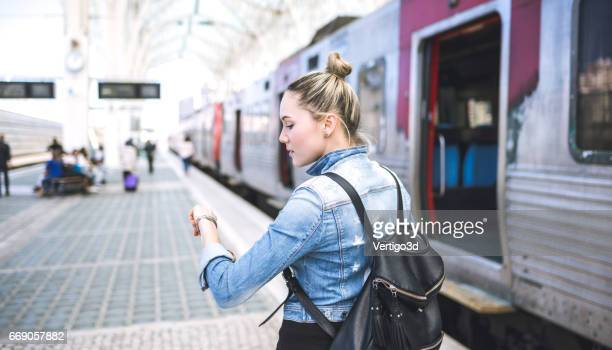 Woman traveler with backpack on rail station checking time