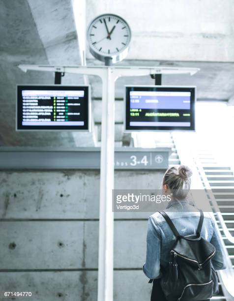 Woman traveler with backpack on station checking in time board