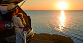 Woman traveler with dog sitting in car trunk near sea, watching sunset.
