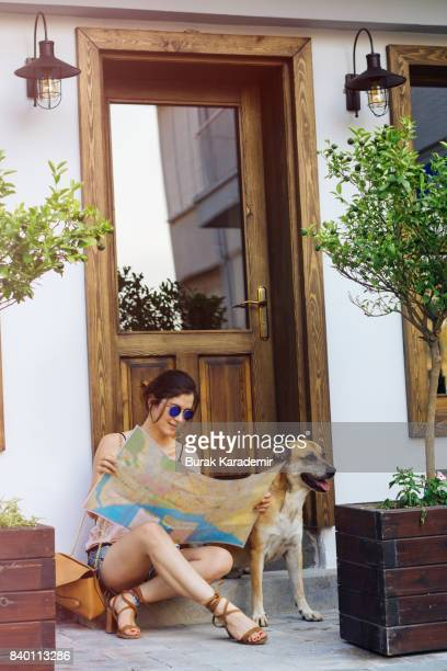 Woman traveler with dog using world map