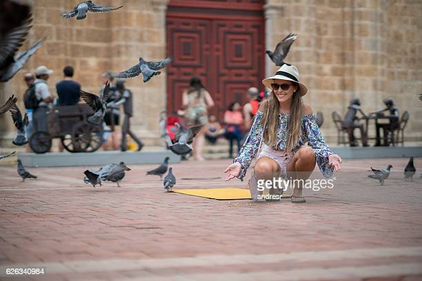 Woman traveling and feeding doves in Cartagena