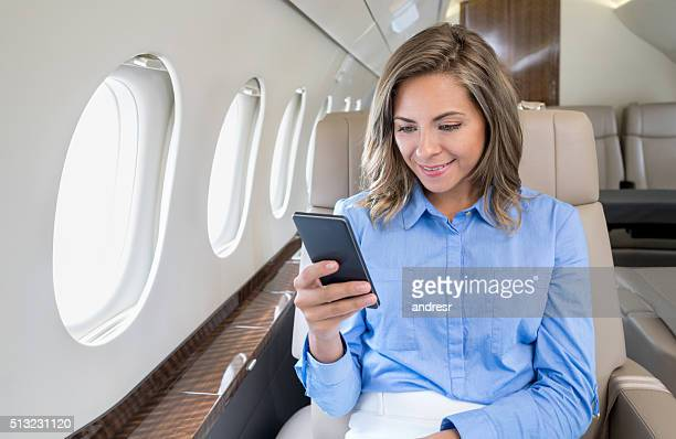 Woman traveling by air and texting on the plane