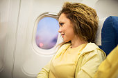 Smiling young woman enjoying while flying by airplane.