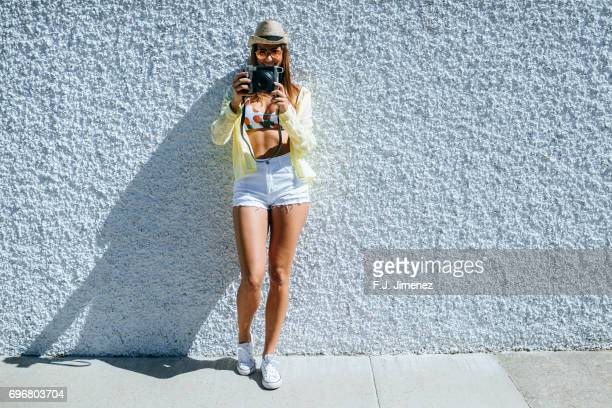 Woman traveling in front of white wall