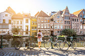Sunrise view on the water channel with beautiful old buildings with woman standing near the bicycles in Gent city