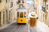 Young woman tourist photographing famous retro yellow tram on the street in Lisbon city, Portugal