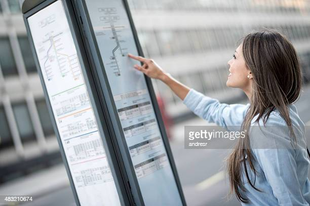 Woman traveling in London and looking a the bus schedule