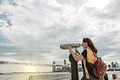 Woman traveling in New York using the tourist binoculars