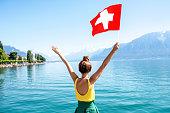 Young female traveler with swiss flag enjoying great view on Geneva lake in Switzerland
