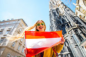 Young smiling woman holding austrian flag with St. Stephen's Cathedral on the background in Vienna