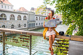 Young female traveler in yellow sweater and sunglasses sitting with map on Butchers bridge in the center of Ljubljana city in Slovenia. Traveling Slovenia