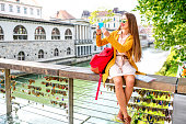 Young female traveler in yellow sweater and sunglasses maling selfie photo with phone sitting on Butchers bridge in the center of Ljubljana city in Slovenia. Traveling Slovenia