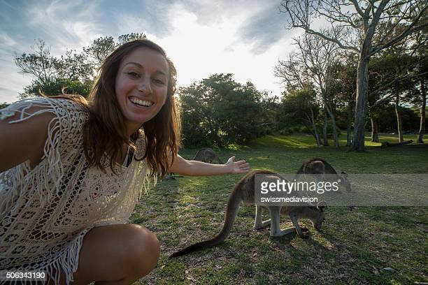 Woman traveling takes selfie portrait with kangaroos on background